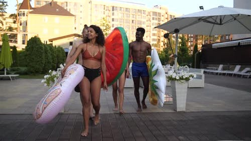 Group of Diverse Friends Walking To Pool at Hotel