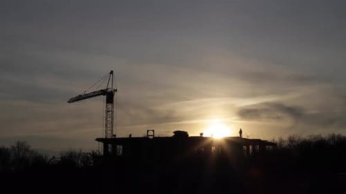 Construction site with big tower crane in time lapse with cloudscape.