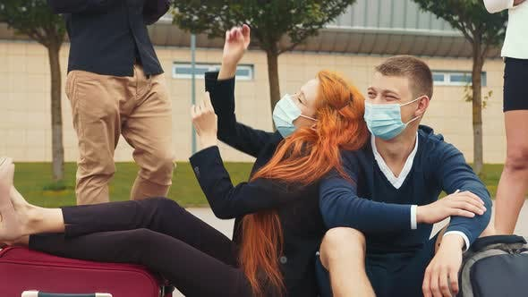 A Tourist Group in Medical Masks Who Are Having Fun Waiting for Their Flight. Young Happy Girl in a