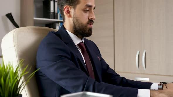 Thumbnail for Serious Geschäftsmann in seinem Büro binden seine Krawatte