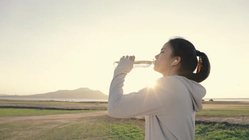Athlete woman runner drinking water after running fitness workout.
