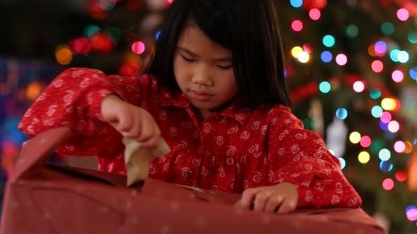 Young girl opens  Christmas present