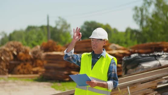 Thumbnail for Male Worker Examining Plank's Stack