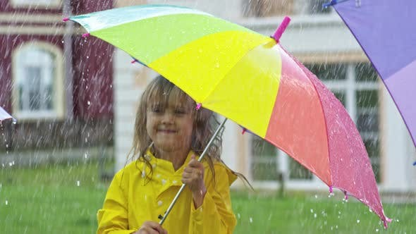 Thumbnail for Cute Girl in Yellow Raincoat Jumping in Rain