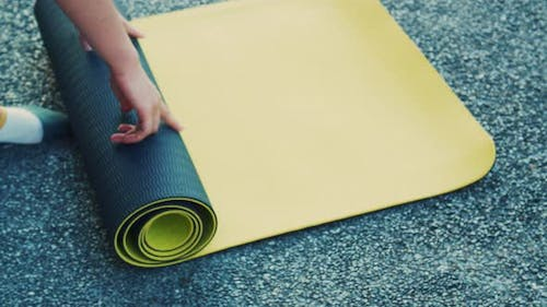 Close up of Asian female rolling yoga mat in a yoga class in the park.