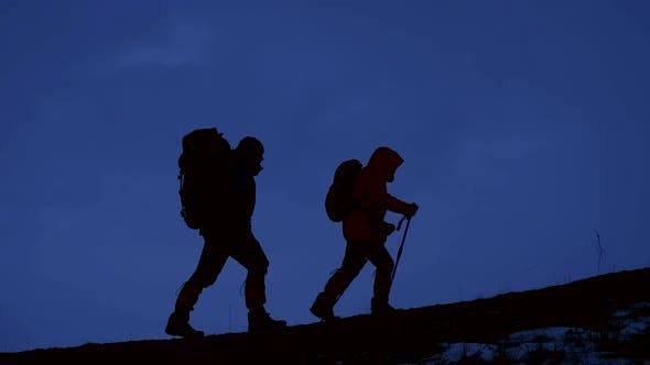 Thumbnail for Two Hikers Going Up on the Mountain at Night with Bags of Equipment and Food