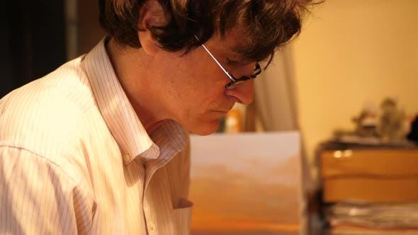 Thumbnail for Ein Künstler malt ein Ölgemälde auf Leinwand in seinem Kunststudio.