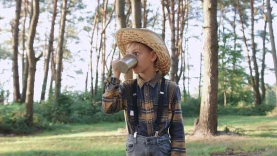Thumbnail for Kleiner Junge im Hut, der Tee im Grünen Park am sonnigen Tag trinkt
