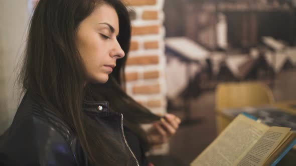 Thumbnail for Close Look of a Beautiful Woman Playing with Her Hair While Reading a Book in Coffee Shop