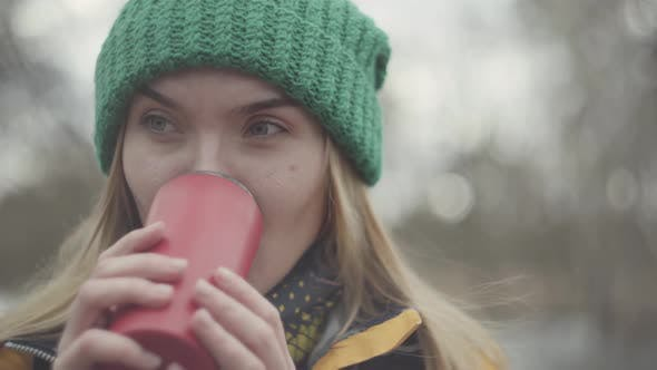 Thumbnail for Close Up Portrait of Pretty Woman in Green Hat and Yellow Coat Drinking Tea or Coffee From the