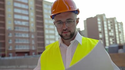 Man Looks in White Paper with House Project