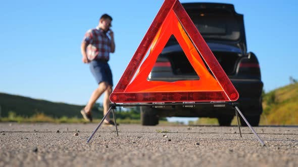 Thumbnail for Close Up of Red Emergency Stop Sign Standing on Road. Worried and Angry Driver Walking Near His