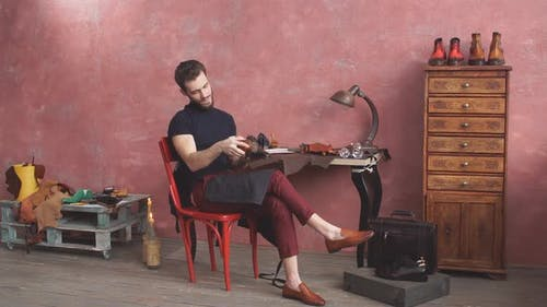Young Man Cleaning Leather Boots While Sitting on Chair