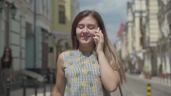 Cover Image for Cute Young Woman Walking Around the Old European City, Talking on the Phone