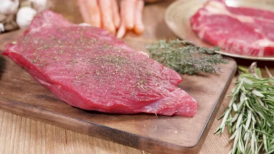 Cover Image for Fresh, Raw Steak, Well Seasoned on a Wooden Board with Thyme and Rosemary