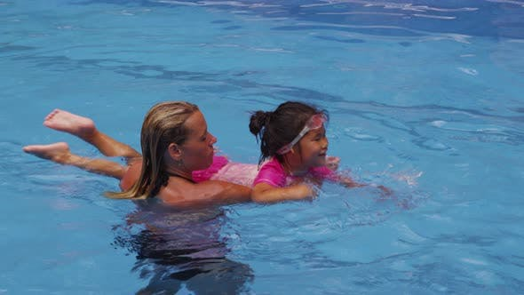 Thumbnail for Mother teaching daughter to swim in pool. Shot on RED EPIC for high quality 4K, UHD, Ultra HD resolu