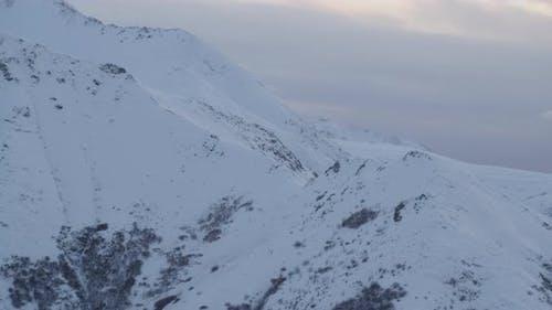 Zoomen Sie auf Alaska State Trooper Hubschrauber fliegen Hubschrauber vor den Bergen, Drohne nen-Antenne