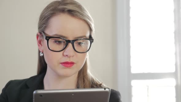Thumbnail for Young Female Business Entrepreneur Presses And Swipes Across Her Tablet 2
