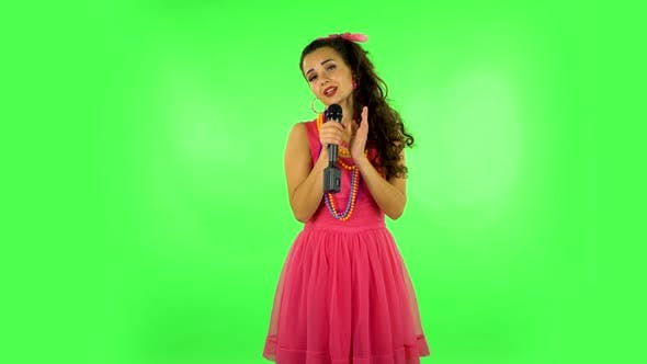 Thumbnail for Attractive Girl Sings Into a Microphone and Moves To the Beat of Music. Green Screen