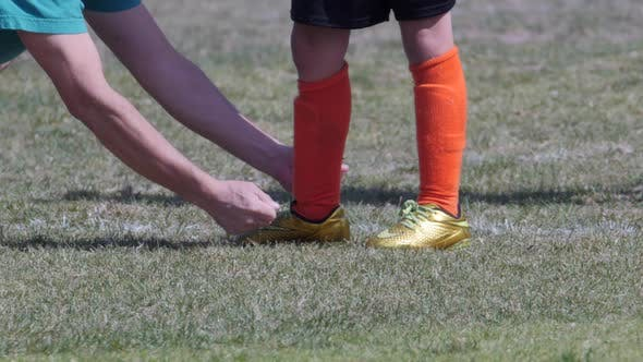 Thumbnail for Youth boys soccer coach tying players shoe.