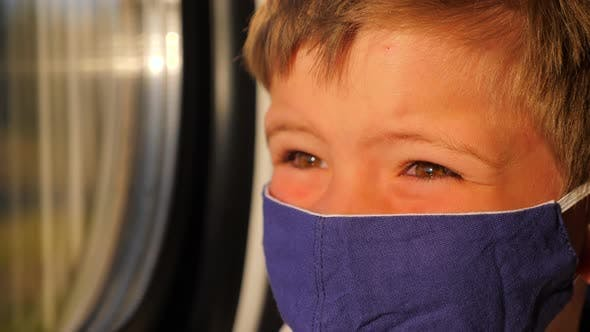 Thumbnail for Boy Looking in the Window During Train Ride. Close-up of Kid in Cotton Facemask. Sun Light on the