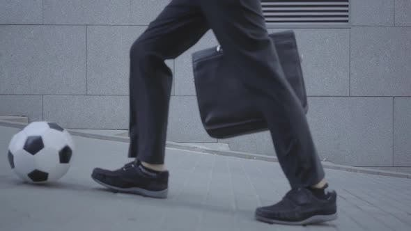 Thumbnail for Feet of Well-dressed Boy Walking on the Street Leading the Ball and Holding Purse