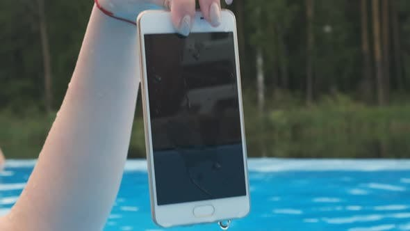 Thumbnail for Close-up Hand of a Girl Holding a Wet Smartphone.