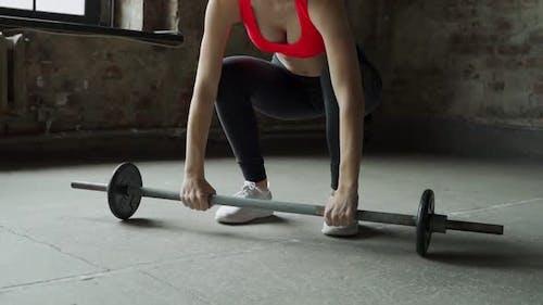 Fitness-Frau führt Langhantel-Lifting im Fitnessstudio