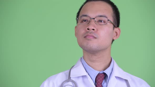 Cover Image for Face of Happy Asian Man Doctor with Eyeglasses Thinking and Looking Up