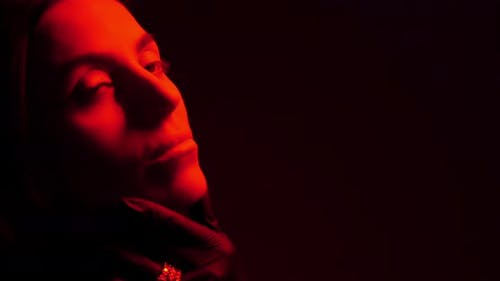 Female Face In The Dark Illuminated By Red Light