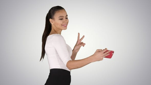 Young brunette taking selfie photo on smartphone smiling