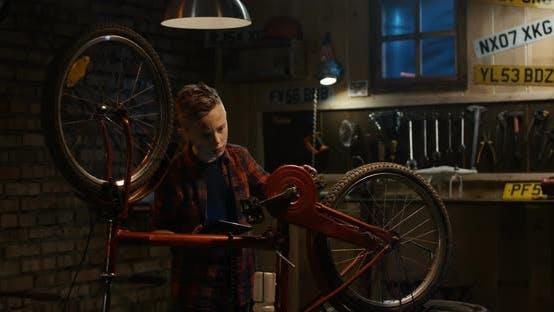 Teen Boy Repairs Bicycle