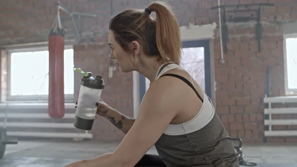 Thumbnail for Tattooed Woman Drinking Water on Tire in Cross Training Gym