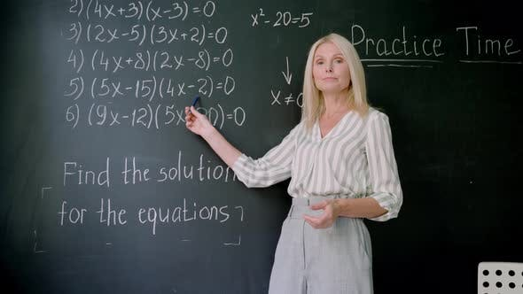 Webcam View of Teacher Explaining Math Formulas on Online Lesson at Chalkboard