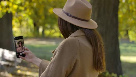 Thumbnail for Back View of Young Caucasian Girl in Brown Hat and Coat Taking Selfie on Smart Phone. Pleasant