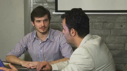 Young Businessman Having a Meeting at the Office with His Mature Colleague