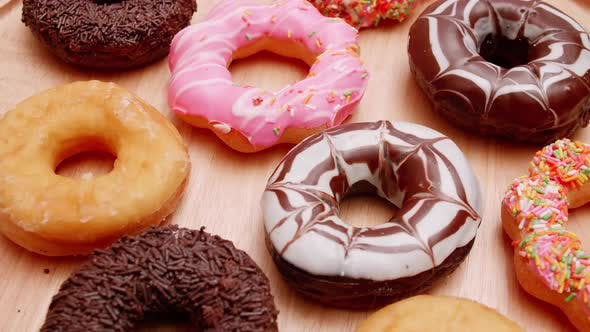 Various flavors of donuts on a rotating wooden plate.