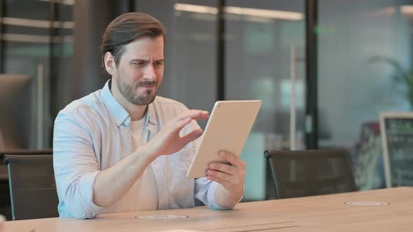 Man Reacting to Loss on Tablet