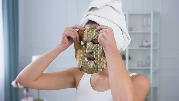 Thumbnail for Young Caucasian Woman Applying Rejuvenating Cosmetic Golden Tissue Mask on Face.