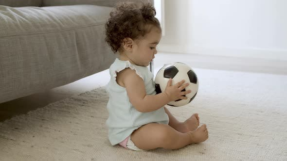 Serious Pretty Girl Sitting on Floor Holding Ball in Hands