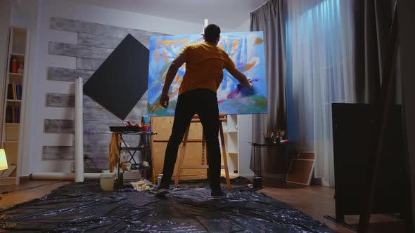 Guy Painting on Canvas with Roller