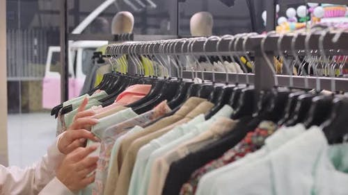 Female in a Clothing Store Chooses a Dress Blouse to Buy Closeup on Hands