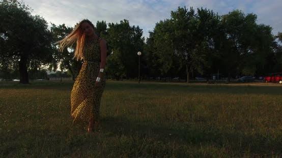 Thumbnail for Beautiful women walking barefoot in grass at sunset