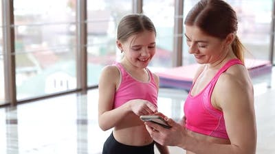 Mom and daughter train in the gym. The daughter repeats her mother's movements