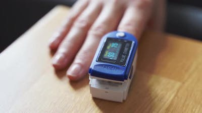 Woman at Home with Pulse Oximeter on Finger