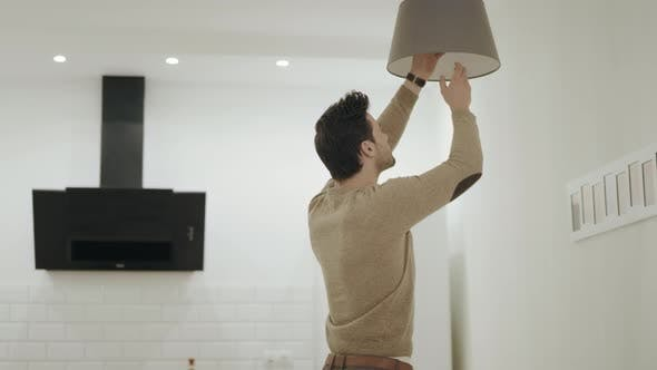Thumbnail for White Man Unscrewing Light Bulb at Open Kitchen. Guy Standing Under Chandelier