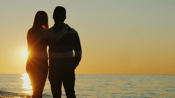 Cover Image for Silhouettes of a Young Couple Hugging and Admiring the Sunset Together By the Sea