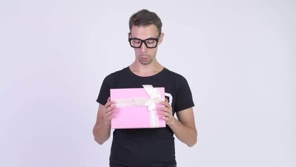Thumbnail for Studio Shot of Happy Nerd Man Holding Gift Box