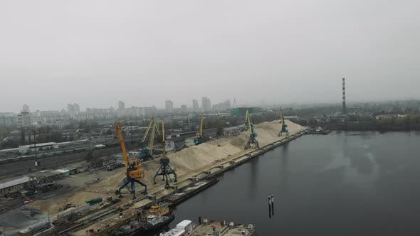 Thumbnail for Aerial view of industrial city in smog and fog with construction cargo cranes working at docks