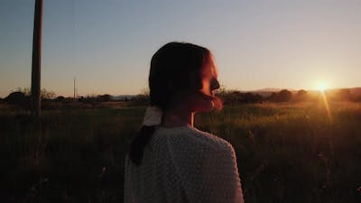 Girl walks carefree in a field at sunset